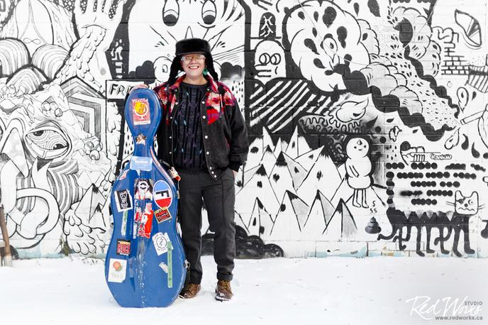 Cris Derksen with cello and case standing in front a graffiti brick wall. Part of the High Performance Rodeo