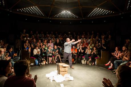 Every Brilliant Thing performance with Jonny Donahoe performing on stage with arms out reached to an audience surrounding the stage.  Part of the High Performance Rodeo