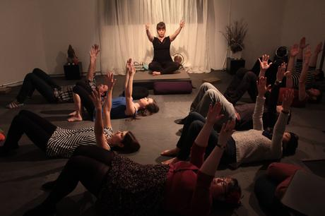 Performer Emelia Symington Fedy sitting on top of a desk with arms reached out while surrounded by audience members laying on the floor on yoga mats during the performance of Through The Gaze of a Navel, part of the High Performance Rodeo