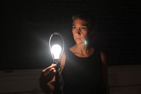 Artist Michelle Polak holding up a lamp with the light turned on and the lamp shade removed, staring into the light during the performance of Trace, part of the High Performance Rodeo