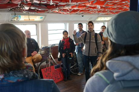 Audience and artists performing together on a ferry boat in the location based performance of Why We Are Here!  Part of the High Performance Rodeo