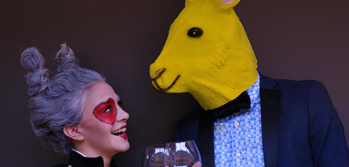 Artists Jessica Barrara and Brett Dahl toasting with glasses of red wine. One in a yellow rabbit mask and the other with hair in the shape of rabbit ears and a heart painted over her eye. Part of the High Performance Rodeo and One Yellow Rabbit.