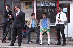 A bus stop filled with busy businessmen while two brothers sit on the bus bench together facing each other; one in knee-high socks and shorts while the other is in a suit.