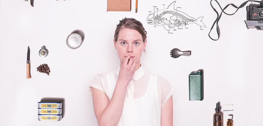 A white wall filled with an drawing of a whale.  A woman is standing in front of the wall looking at the camera.
