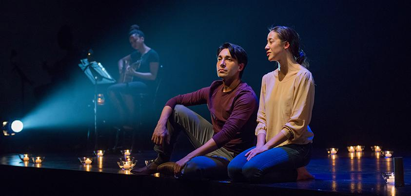 A man and woman sitting up-right on a stage, surrounded by a circle of lit candles.