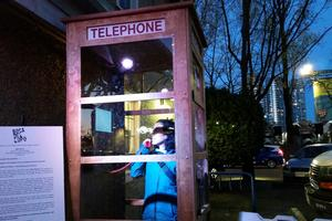 A woman is standing in a outdoor retro phone booth late at night.  The nearby trees have no leafs. She is wearing a winter jacket.  Her hand is holding a retro phone receiver that is attached to a telephone inside the phone booth.