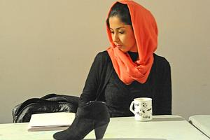 A woman sits at a desk facing sideways while a single black shoe sits upon her desk.