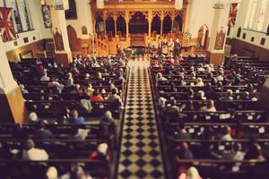 Overhead interior image inside of a church, pews filled.  At the alter is a piano and 4 people standing beside it with mouths open.