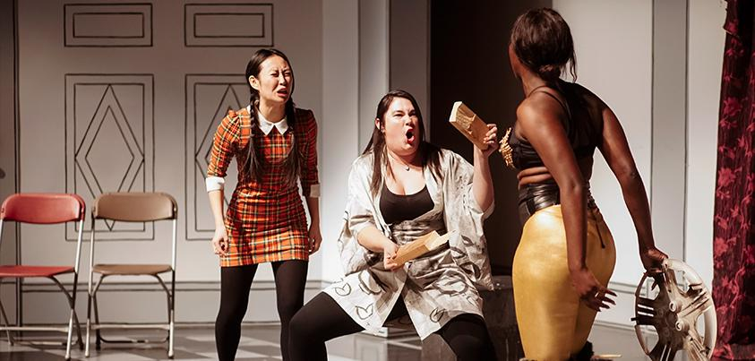 3 women on a stage.  One is crying, one is stanched with knees bent and arms stretched out in ninja arms. Third woman is holding a shield and wearing spandex about to fight with the ninja.