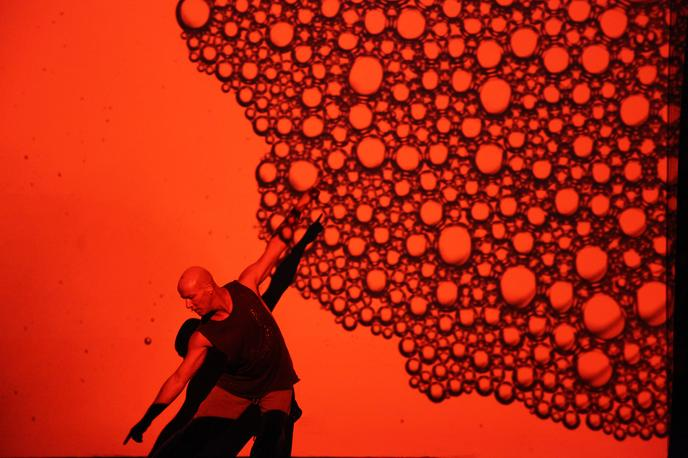 Australian performer posed in a movement with arms angled upwards and legs pointed straight, surrounded by a backdrop of red blood cells for Blood on the Dance Floor part of the High Performance Rodeo. Tickets on sale now for January 24 to 26 performances