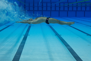 Olympic swimmer underwater in a pool swimming with arms stretched out and oxygen bubbles releasing from his mouth.