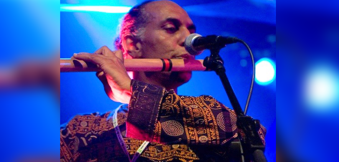 Prashant John holding a wooden flute to a microphone and playing music as part of the High Performance Rodeo