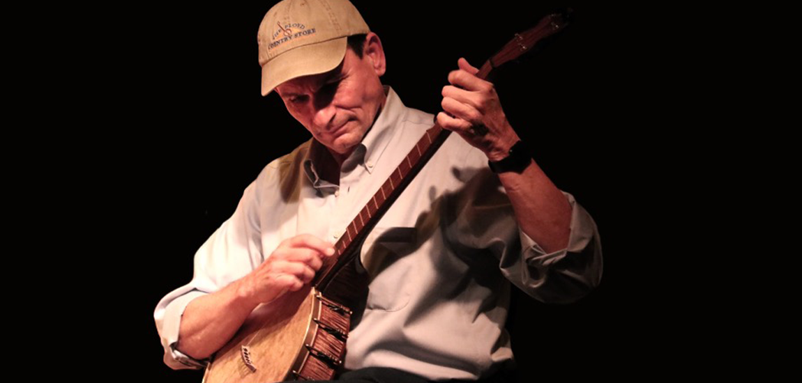 A performer on stage holds a banjo instrument in their hands, plucking the strings