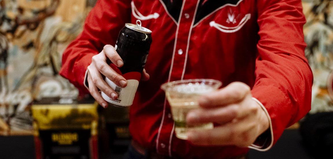 A bartender dressed in black and red cowboy shirt is holding out a poured drink towards the camera inviting you to take it